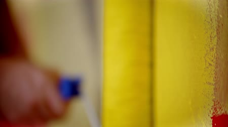 splattered : Painting a wall with a yellow color paint using a roller Stock Footage