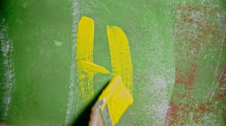 dekoratör : A person writing HI on the green wall with a yellow paint
