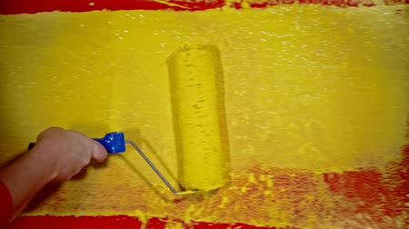 decorador : Painting a wall with a yellow color using a roller