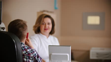 slit : Ophthalmologist treatment - mature woman doctor sitting by the table with a little boy - giving the boy an eye shield Stock Footage