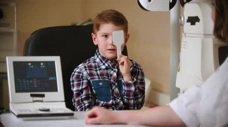 optyk : A treatment in eye clinic - a little boy covering his eye with an eye shield