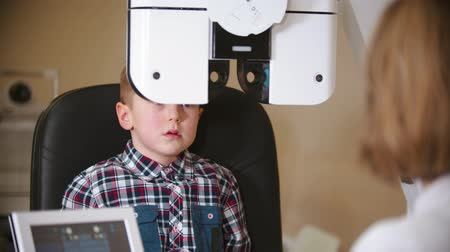 slit : A treatment in eye clinic - checking little boys eye vision with a big special device