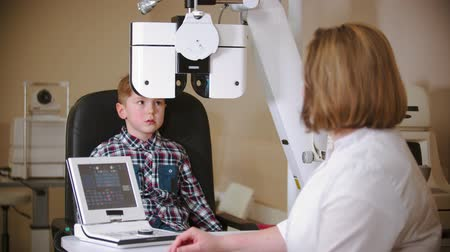 yarık : A treatment in eye clinic - checking little boys eye vision by looking through big special device