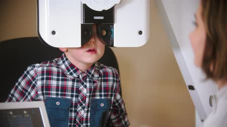 slit : A treatment in eye clinic - checking little boys eye vision by looking through big special device with lenses