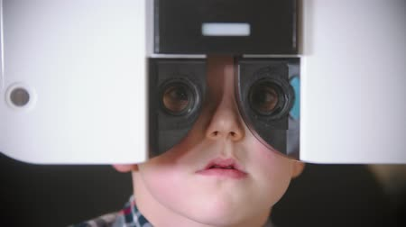 slit : A treatment in eye clinic - checking little boys eye vision by looking through big special device with interchangeable lenses Stock Footage