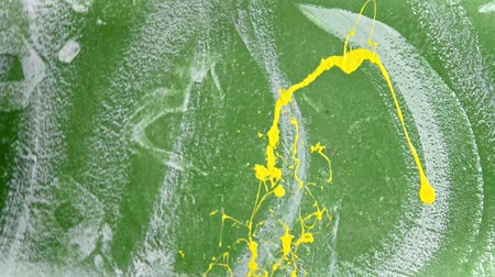 splattered : A person splashes bright yellow color paint on the wall using a brush