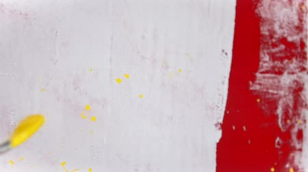 splattered : A person splashes bright yellow color paint on the white wall using a brush