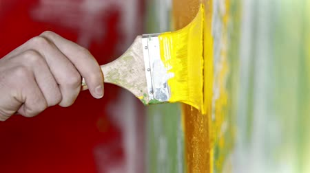 dekoratör : Painting wall with yellow color paint using a brush - interior design