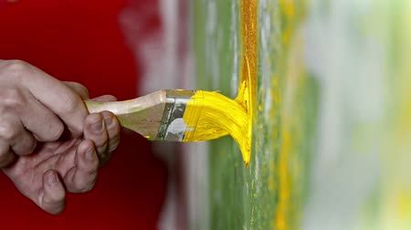 splattered : Pushing the brush covered in yellow paint into the wall - interior design Stock Footage