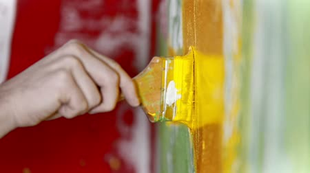 splattered : Painting wall with yellow color paint using a brush - special interior design for the new apartment Stock Footage