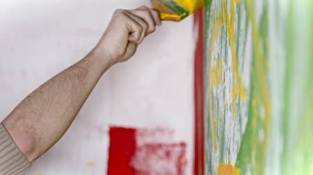 splattered : Hand writes something with a yellow paint on the white and green wall