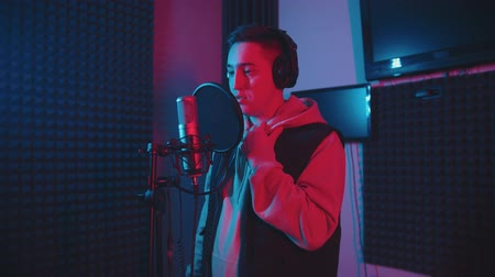vokal : A man with short hair rapping in the studio Stok Video