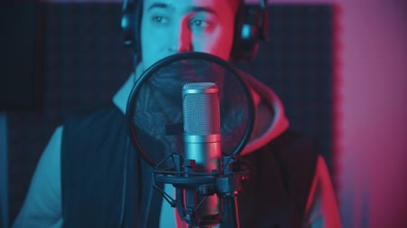 vokal : A man in hoodie rapping in the studio and recording his track wearing headphones