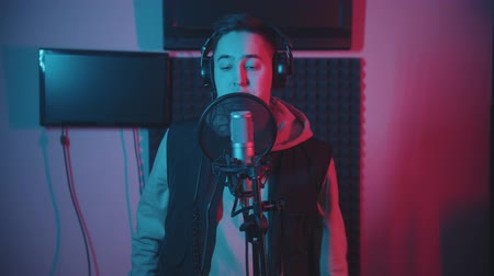 рэп : A man in hoodie rapping in the record studio gesticulates while recording his track