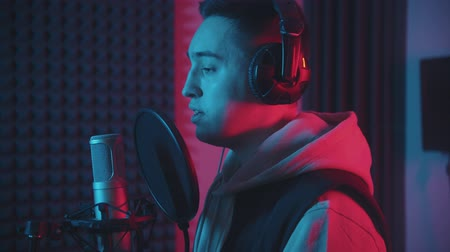 vokal : A man in headphones rapping through the pop-filter in the microphone - studio in neon lighting
