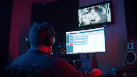 vokal : A man sound engineer in headphones recording audio tracks for a young man rapper - working in neon lighting Stok Video