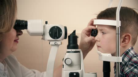 yarık : Boy having a treatment in eye clinic - a woman doctor checking little boys eye vision by looking through big special device using a lens and bright lighting
