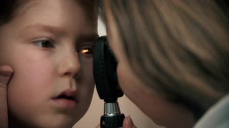 slit : Little boy having a treatment in eye clinic - a woman doctor checking the eye vision by using a device with bright lighting going through the pupil
