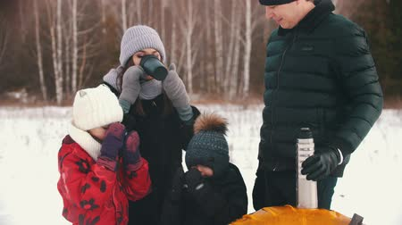 banliyö : Family drinking hot drinks from the termos near the winter forest Stok Video