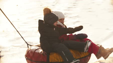 пригородный : A man father rolls his kids on the inflatable sled around himself