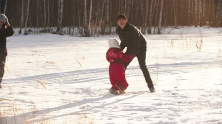 пригородный : A mother and father playing with their kids outdoors in winter Стоковые видеозаписи