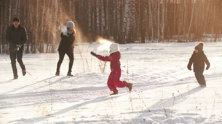 banliyö : Family throwing snow on each other in winter time on sunset