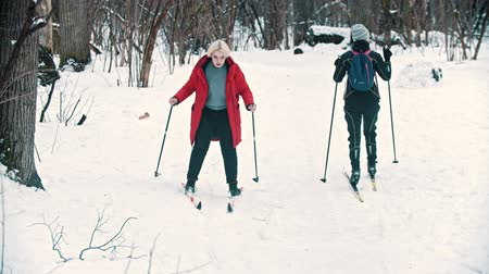 snowbord : A blonde woman walking on ski in the woods