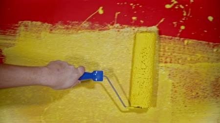 splattered : Hand painting a wall with a yellow color paint using a roller