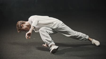 breakdancing : Young man training his dancing in the studio - leaning on his hand and keeps the balance Stock Footage