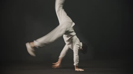 hiphop : Young man dancer showing breakdance tricks in the dark studio Stock Footage