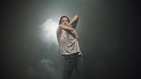 energy balance : A woman in white t-shirt dancing with her hands in the smoky studio