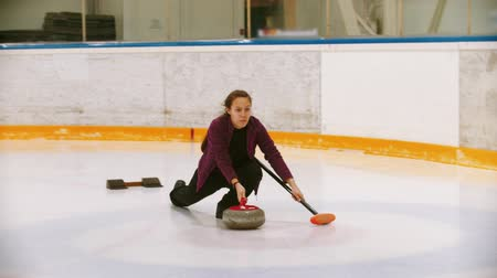 gránit : Curling - a young woman pushes off in the ice field with a granite stone Stock mozgókép