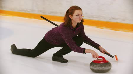 gránit : Curling - a young woman in glasses pushes off in the ice field with a granite stone Stock mozgókép