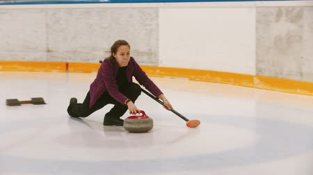 gránit : Curling - a woman pushes off on the ice field with a granite stone holding a brush Stock mozgókép