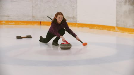 gránit : Curling - a woman in glasses pushes off on the ice field with a granite stone holding a brush Stock mozgókép