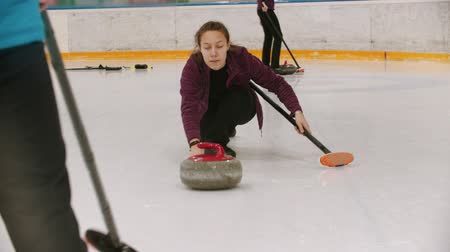 gránit : Curling - a woman skating on the ice field with a granite stone and releasing it