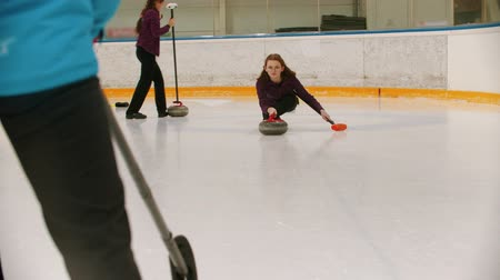 規律 : Curling training - a woman skating on the ice field with a granite stone and releasing it 動画素材