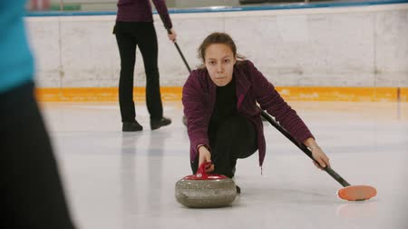 gránit : Curling - a woman skating on the ice field and leading a granite stone Stock mozgókép