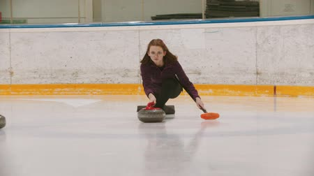 sporty zimowe : Curling - a woman in glasses skating on the ice field and leading a granite stone