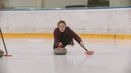 gránit : Curling - a woman in glasses skating and leading a granite stone on the ice field