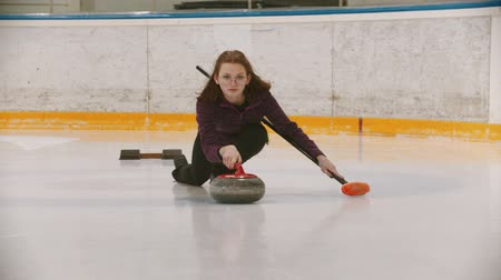 gránit : Curling - a woman in glasses skating and leading main granite stone on the ice field Stock mozgókép