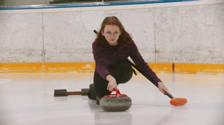 gránit : Curling training - a woman in glasses skating and leading main granite stone on the ice field Stock mozgókép