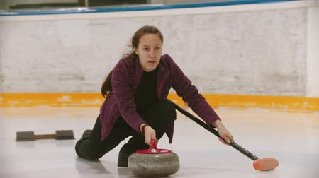 определенный : Curling - a woman in glasses skating on the ice field and leading a granite stone to the certain point