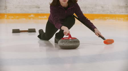 определенный : Curling - a woman in glasses skating on the ice field and leading a granite stone to the certain point holding a brush