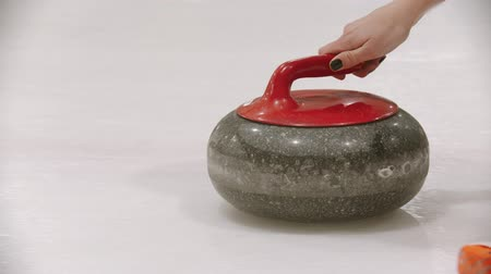 gránit : Curling - a granite stone on the ice field with red handle