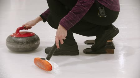 fegyelem : Curling - a young woman pushes off from the stand with granite stone