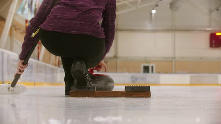 fegyelem : Curling training - a woman pushes the granite stone forwards