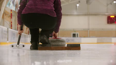 gránit : Curling training in sport complex - a woman pushes the granite stone forwards Stock mozgókép