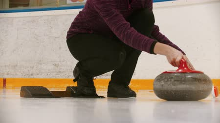 fegyelem : Curling in sport complex - a woman pushes the granite stone forwards