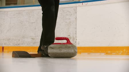 gránit : Curling - a womans hand pushes off from the stand with granite stone Stock mozgókép
